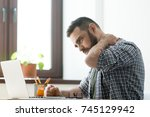 Small photo of Troubled bearded man massages aching neck with a pained expression, working on laptop computer, deep in thoughts.