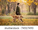 Stock photo a girl and her dog labrador retriever walking in a park in autumn 74517493