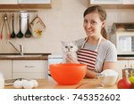 Small photo of The young beautiful happy woman with a white Persian cat prepares dough for Christmas cakes with tablet on table in the kitchen. Cooking home. Prepare food.