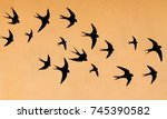 Stock photo silhouettes of many swallows on a orange background 745390582