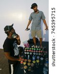 Small photo of MMRDA Exhibition Grounds, BKC Rd, Mumbai, Maharashtra, India - October 27, 2017 - Young artists are discussing and using spray paint cans to make a graffiti art, at the Abu Dhabi week exhibition.
