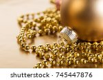 Small photo of Closeup shot of hold shiny ball for Christmas tree composed with adorned garland.