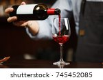 Waiter Pouring Red Wine Into...