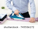 Small photo of Man ironing shirt on ironing board. Steaming blue iron. Clothes ironing board household concept