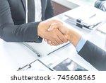 businessmen shaking hands ... | Shutterstock . vector #745608565