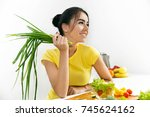 smiling woman holds green onion ...