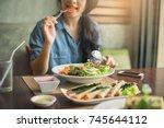 closeup of a woman eating... | Shutterstock . vector #745644112