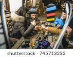 Small photo of Happy friends drinking beer and eating chips at after ski - Friendship concept with cheerful people having fun at bar restaurant resort with snow equipment - High iso image with shallow depth of field