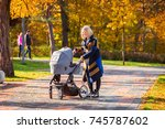 a young mother with a stroller... | Shutterstock . vector #745787602