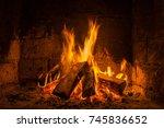 a fire burns in a fireplace ... | Shutterstock . vector #745836652
