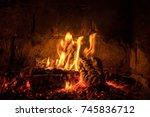 a fire burns in a fireplace ... | Shutterstock . vector #745836712