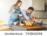 young married couple in kitchen.... | Shutterstock . vector #745842058