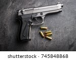 9mm pistol bullets and handgun on black table.