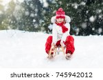 little girl enjoying a sleigh... | Shutterstock . vector #745942012