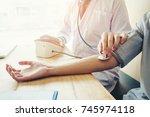 doctor measuring arterial blood ... | Shutterstock . vector #745974118