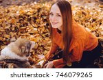 Stock photo smiling girl lies in autumn foliage with her dog 746079265