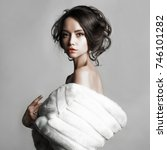 Small photo of Fashion studio portrait of beautiful lady with elegant hairstyle in white fur coat. Winter beauty in luxury. Fashion fur. Beautiful woman in luxury fur coat. Fashion model posing in eco-fur coat