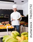 smiling male cook deciding on... | Shutterstock . vector #746201752