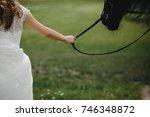bride walks with black horse on ... | Shutterstock . vector #746348872