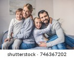 happy parents and kids sitting... | Shutterstock . vector #746367202