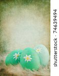 Textured Easter eggs in a nest of feathers against a green vintage background with room for copy space. Extreme shallow DOF. - stock photo