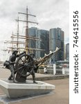Small photo of Sydney, Australia - March 21, 2017: Windjammer Sailors Statue handling ship wheel on southeast quay of Darling Harbour with tall ship behind and HSBC buildings over water. All under heavy gray sky.