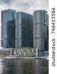 Small photo of Sydney, Australia - March 21, 2017: Closeup of three HSBC office towers on east quay of Darling Harbour under heavy gray sky. Water in front, condominiums and restaurants.