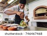 male chef preparing salad in...   Shutterstock . vector #746467468