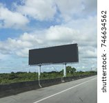 Small photo of black blank billboards or advertising poster on side of express way or overpass on blue sky background in advertise concept