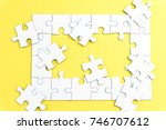 Small photo of half complete white color puzzle on yellow background. Task for completion concept. selective focus