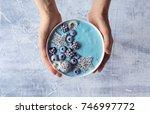 woman's hands holding blue...   Shutterstock . vector #746997772