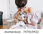 Stock photo close up portrait of beagle dog with big sad eyes and cheerful girl with short haircut holding 747015922