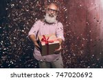 Small photo of Modern senior bearded man gives a gift and happy smile in gold confetti. Happy New Year 2018. Merry Christmas to you!