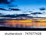 sky with huge grey clouds over... | Shutterstock . vector #747077428