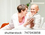 husband and wife chuckling over ... | Shutterstock . vector #747343858