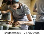 kitchen staff decorating cooked ... | Shutterstock . vector #747379936