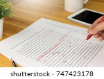 Stock photo hand working on paper for proofreading 747423178