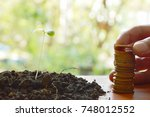 Small photo of hand putting gold coin arrange and little plant in dirt on wooden board