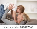 happy mother laying on back on... | Shutterstock . vector #748027366