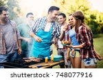 happy friends enjoying barbecue ... | Shutterstock . vector #748077916