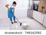 young housemaid cleaning floor... | Shutterstock . vector #748162582