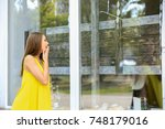 young woman looking at showcase ...   Shutterstock . vector #748179016