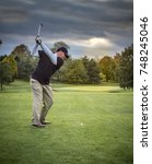 Small photo of Golf shot aiming for the green on a stormy day