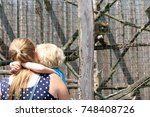 A Mom Holding Her Blond Haired...