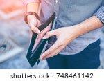 man standing holding black... | Shutterstock . vector #748461142