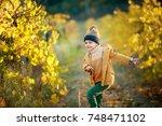 cute little boy in a yellow... | Shutterstock . vector #748471102