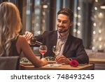 handsome elegant man is pouring ... | Shutterstock . vector #748493245