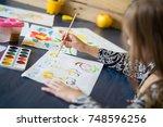 little girl draws paints | Shutterstock . vector #748596256