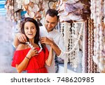 man putting a seashell necklace ... | Shutterstock . vector #748620985