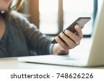 woman use phone on desk in... | Shutterstock . vector #748626226